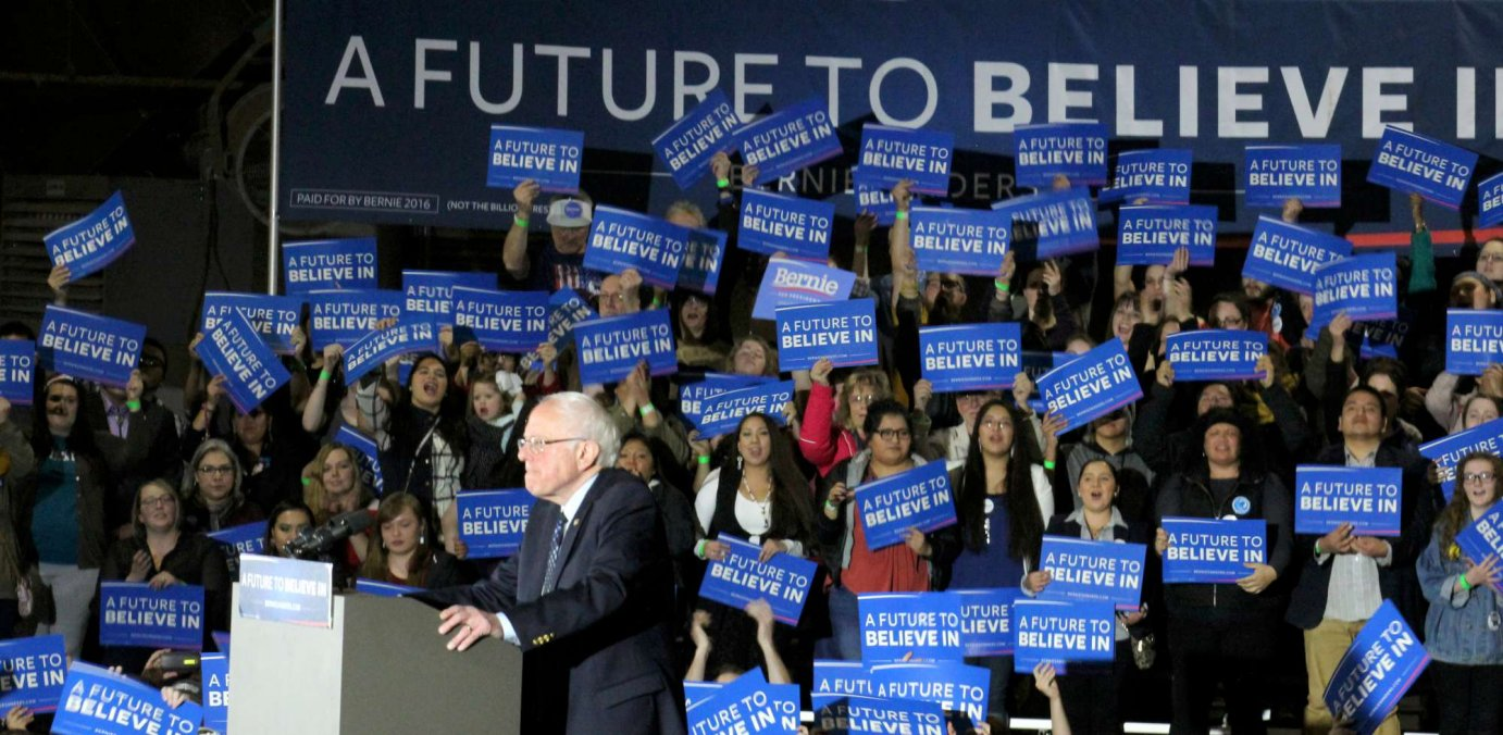 Sanders speaks in front of a backdrop of supporters in Lawrence. (Photo by Nicci Banman / Mary Costello))