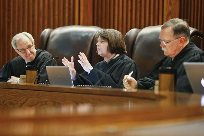 Kansas Supreme Court Justice Marla Luckert (center) and Chief Justice Lawton Nuss (right) are being targeted for defeat when they stand for retention in November. Also being targeted by conservatives are Justices Carol Beier and Dan Biles. (AP photo)
