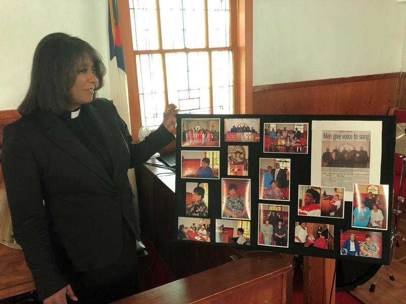 The Rev. Shirley Heermance of St. Mark's AME Church in Topeka looks over an array of photos of Linda Brown. Funeral services for Brown were held Thursday in Topeka. (photo credit: Carla Eckels, KMUW)