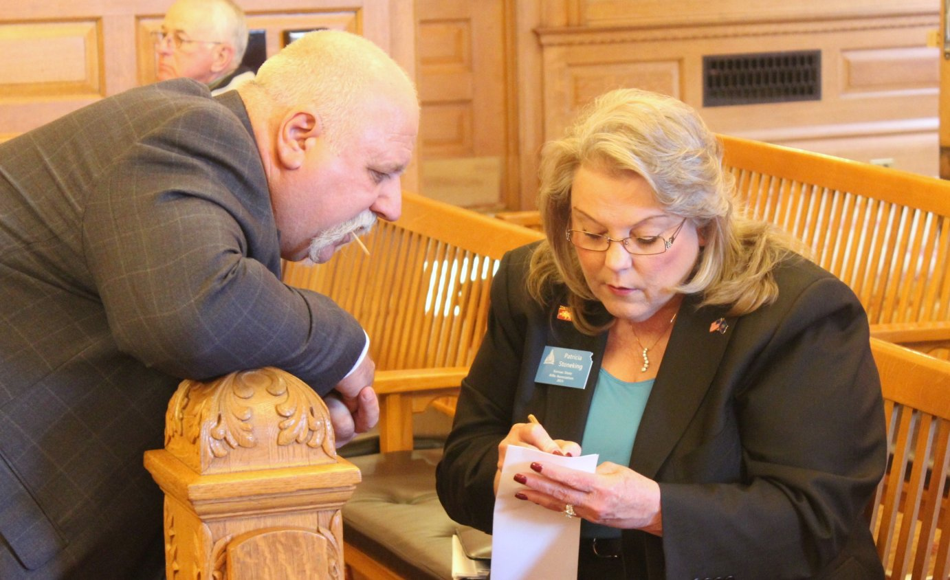 Patricia Stoneking, with the Kansas State Rifle Association, confers with Rep. Michael Houser before a committee meeting on the bill. (Photo by Stephen Koranda)