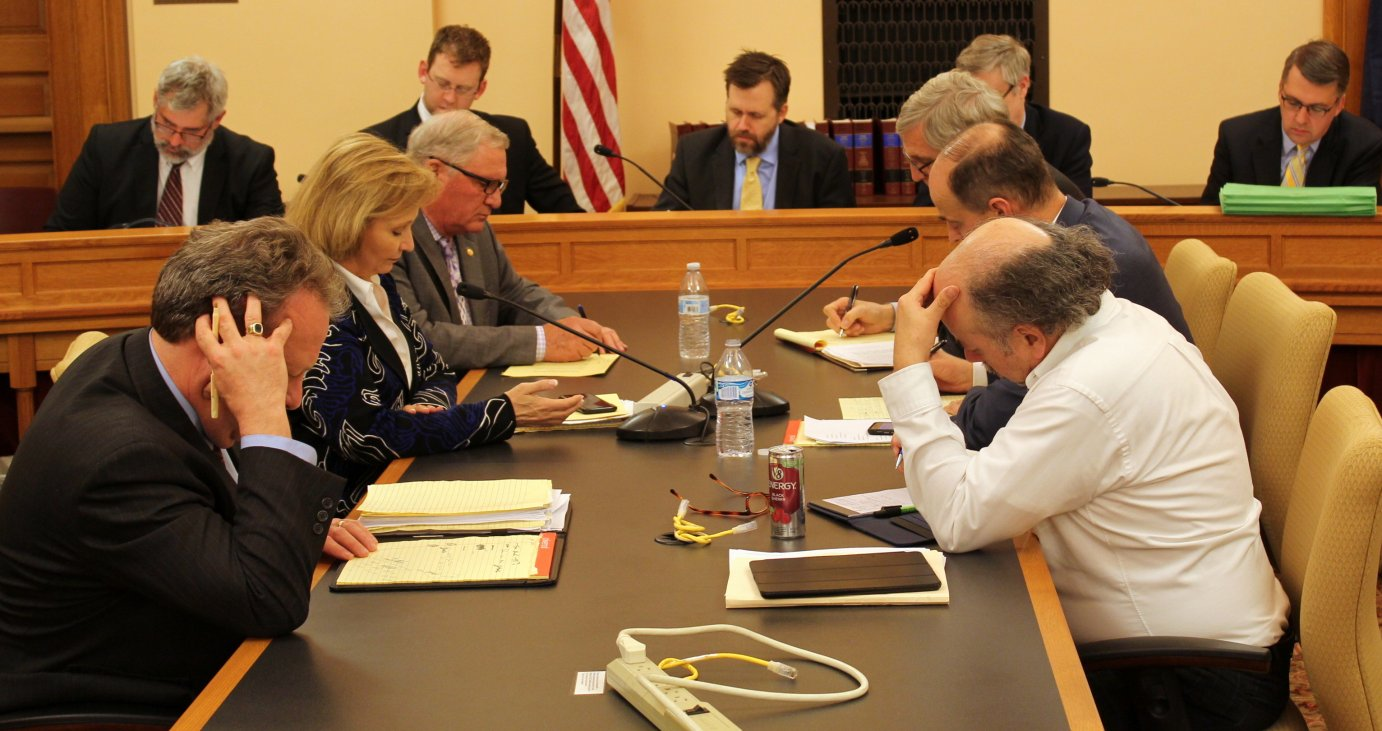 House and Senate negotiators study documents during work on a tax proposal. (Photo by Stephen Koranda)