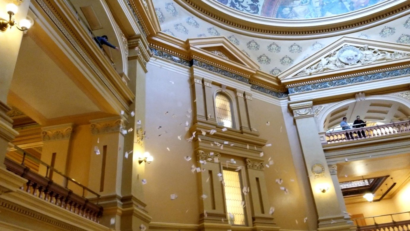 A protester throwing fliers in the Kansas Statehouse. (Photo by Stephen Koranda)
