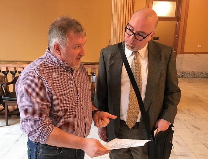 Vape store owner Wally Gibson, left, shows Bert Brown a copy of an ad from a competitor encouraging Kansans to avoid taxes by buying in Oklahoma. Brown leads an advocacy group for e-cigarette users. (Photo: Andy Marso, Kansas News Service)