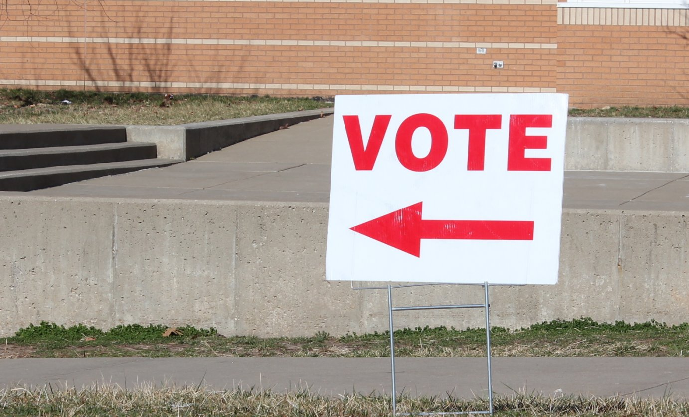 A sign pointing to a polling place during the recent Kansas caucus. (Photo by Stephen Koranda)