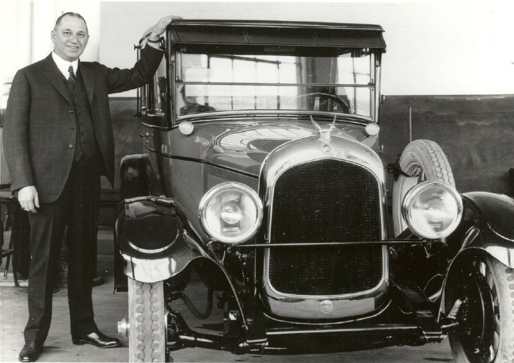 Kansas-born Walter P. Chrysler, standing next to one of the early automobiles his company produced.