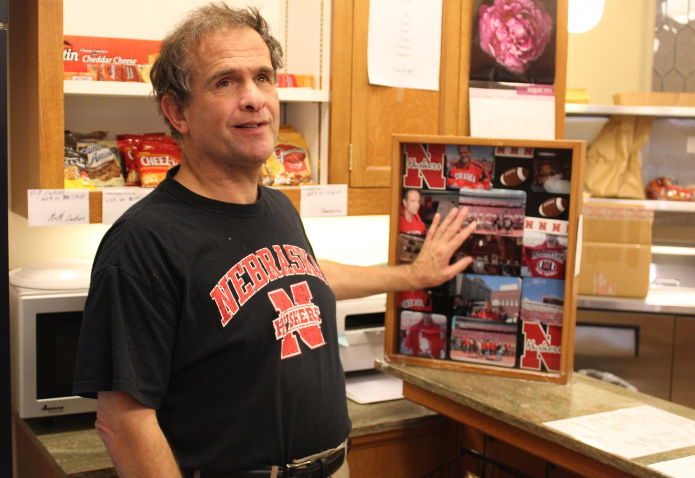 Don Wistuba, a dedicated Huskers fan, shows off some Huskers memorabilia in his snack shop. He's planning to close his doors after nearly 40 years in the Kansas Statehouse. (Photo by Stephen Koranda)