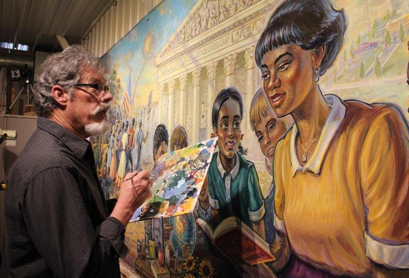 Artist Michael Young adds the finishing touches to the Brown v. Board of Education Mural in his studio in Kansas City, Kansas. Young says it's a dream come true to paint the mural, which visitors can see on display at the Kansas Capitol for years to come.  (Photo by Carla Eckels / KMUW Radio)