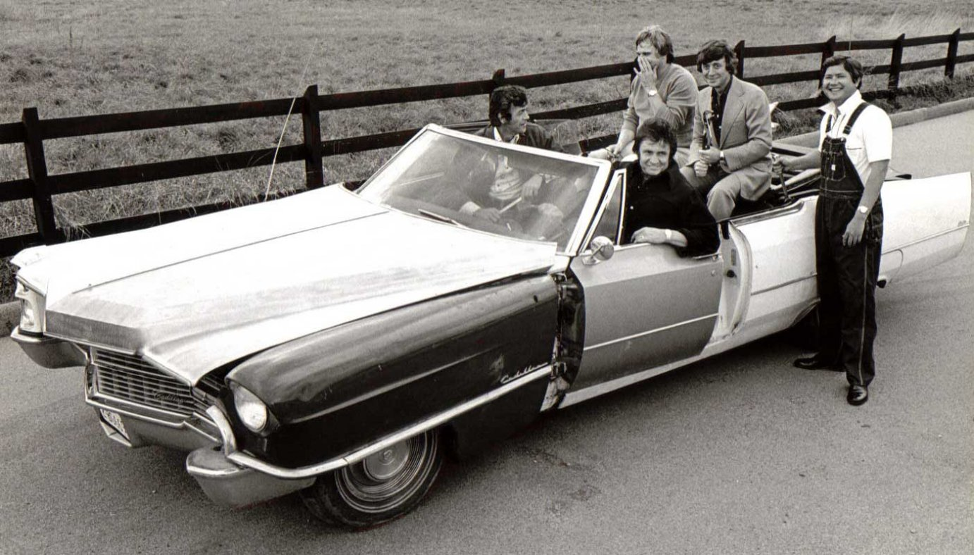 """Johnny Cash and crew in a promo shot for his 1976 hit """"One Piece At A Time"""" (where he steals an entire car, part by part, over several years working at the factory)."""