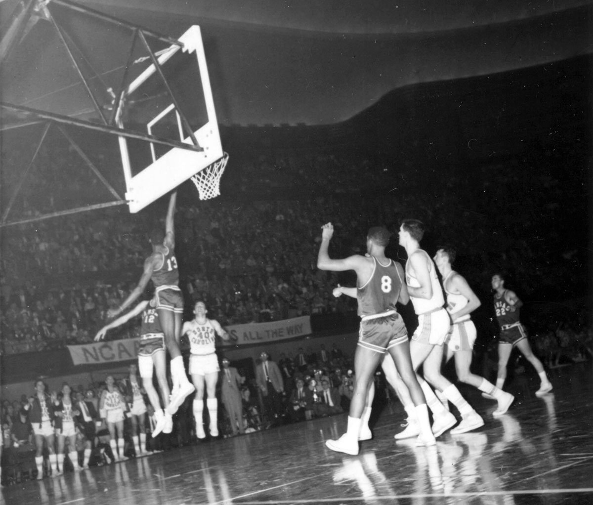 The final seconds of the third overtime in the 1957 final between North Carolina and Kansas. Wilt Chamberlain (13) has just rejected Tommy Kearns' (40) jumper. (Photo via KU University Archives)