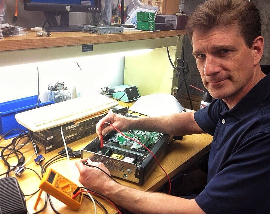 Steve Kincaid, Director of Engineering and interim Director of Kansas Public Radio, replacing the flux capacitor in the station's new time travel app, which should allow us to travel forward in time to correct on-air mistakes and anomolies before listeners can hear them.  Either that, or Steve is simply testing the voltage of some random radio part. You be the judge.