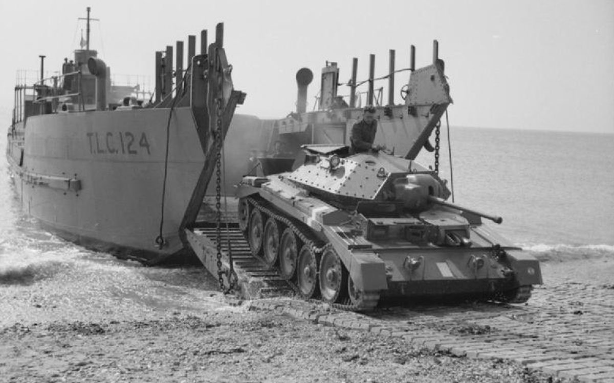 A Crusader I tank emerges from a tank landing craft (TLC 124) during tests of a portable concrete roadway, in this case laid on the beach, 26 April 1942. (Wikimedia)