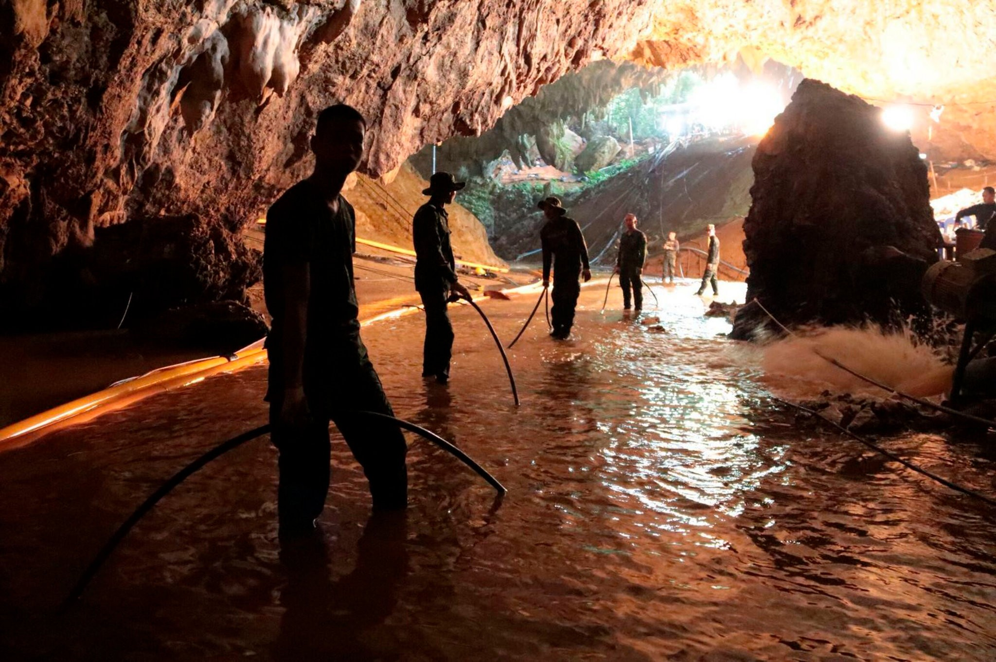 Thai rescue teams arranging a water-pumping system at the entrance to a flooded cave complex where 12 boys and their soccer coach were trapped in Chiang Rai, Thailand. (Photo by Royal Thai Navy)