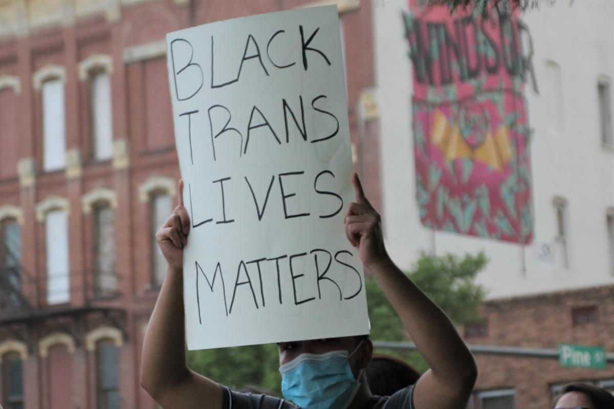 "An attendee holding a ""Black Trans Lives Matter"" sign as dust clouds rolled in. (Photo by Corinne Boyer, Kansas News Service)"