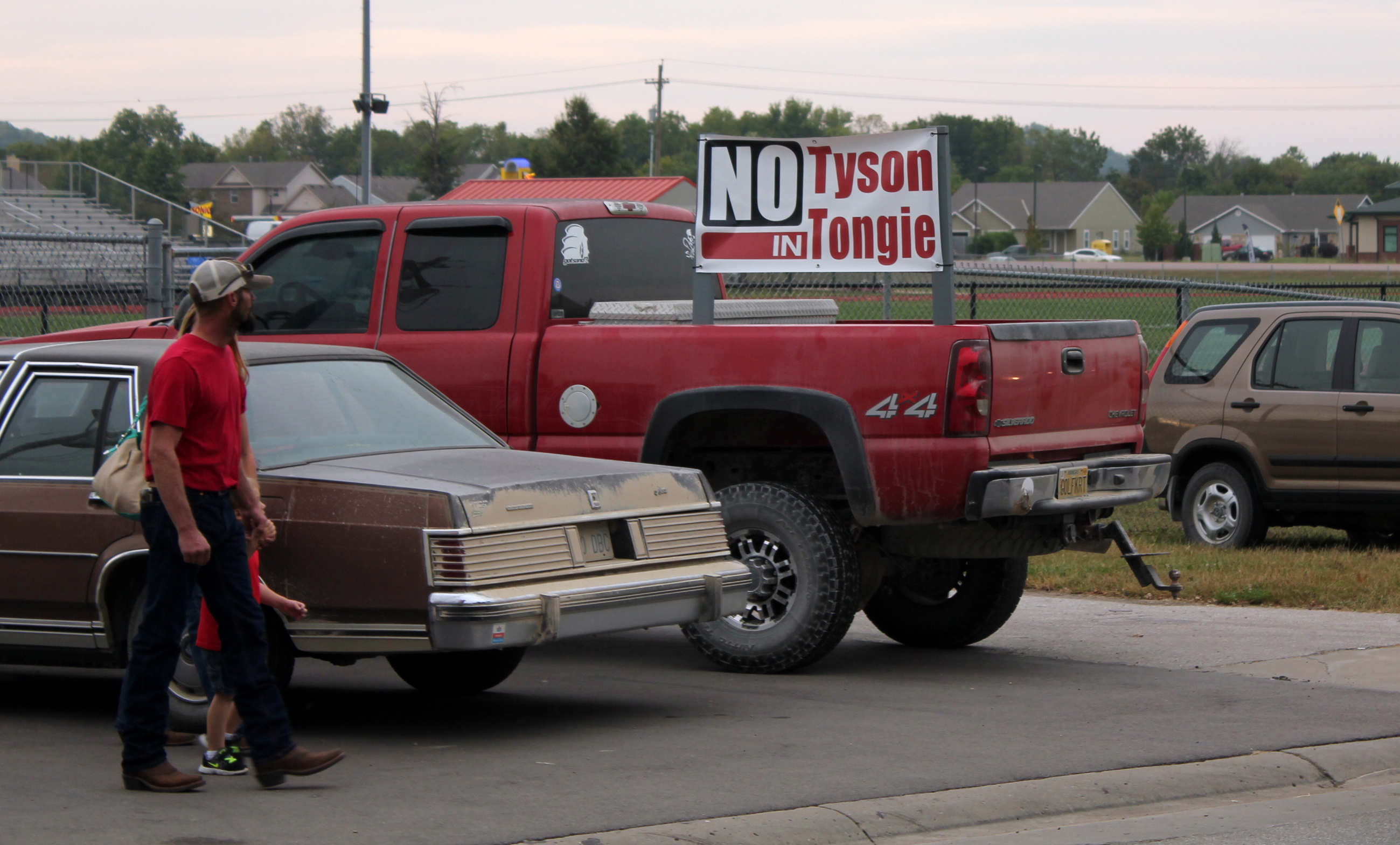 """A """"No Tyson"""" banner pops up from the bed of a pickup truck outside a public meeting last year about the plan for a chicken processing plant in Tonganoxie, Kansas. (Photo by Stephen Koranda)"""