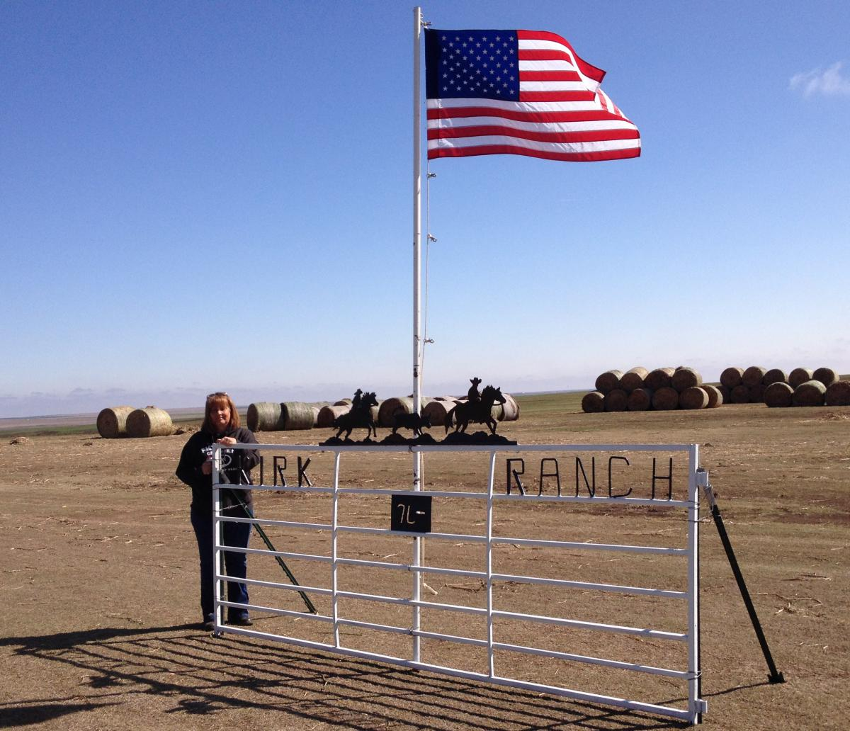 Rancher Gena Kirk stands in front of hay donated for fire-affected ranchers.  (Photo by Bryan Thompson)